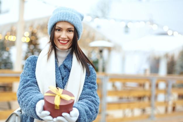 Feliz mujer morena en abrigo de invierno sosteniendo una caja de regalo en la feria de navidad. espacio para texto
