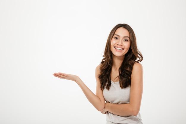 Feliz mujer morena con copyspace en la palma y mirando a la cámara sobre gris
