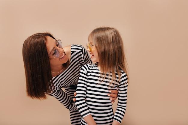 Feliz mujer morena con peinado corto mirando a su encantadora niña sonriente y divertirse sobre fondo aislado