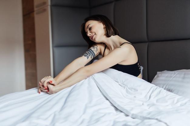 Feliz mujer morena de pelo largo en cama blanca en suave luz de la mañana bajo el edredón
