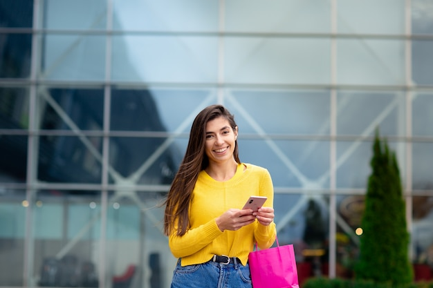 Feliz mujer morena vestida de suéter amarillo, con bolsas de compras y teléfono móvil disfrutando de compras.