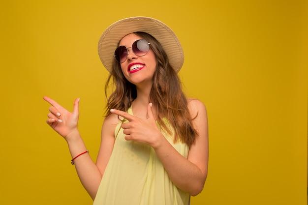 Feliz mujer morena con vestido amarillo y sombrero mira hacia arriba, señalando con el dedo y sonríe sinceramente en la pared amarilla