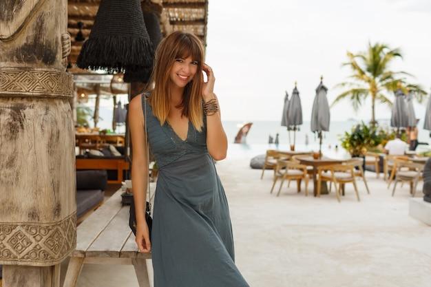 Feliz mujer morena en vestido sexy posando en un elegante restaurante de playa en estilo asiático.