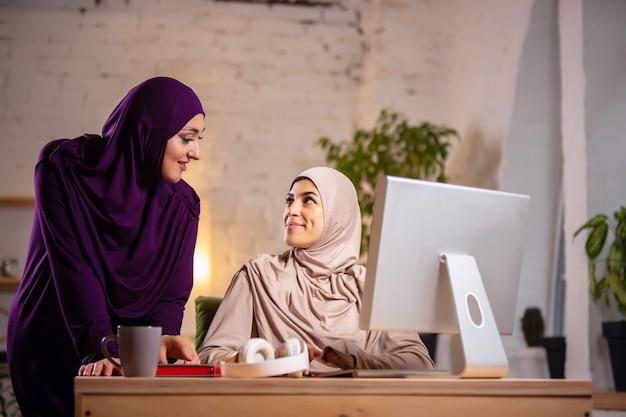 Feliz mujer musulmana en casa durante la lección en línea. tecnologías, educación remota, concepto de etnia