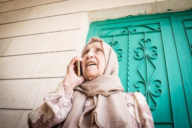 Feliz mujer musulmana senior hablando por teléfono