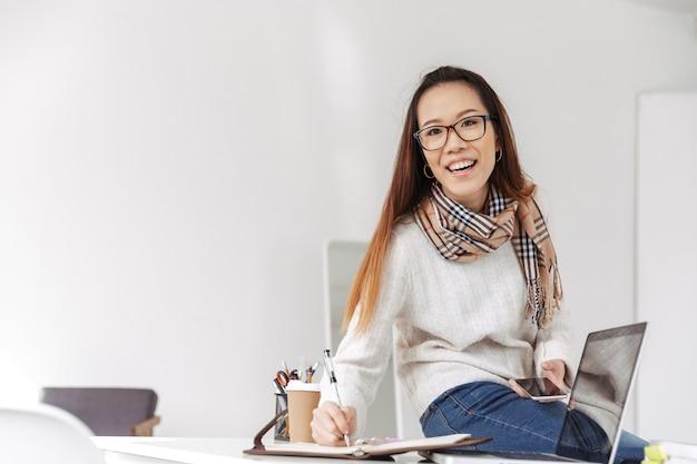 Feliz mujer de negocios asiática en anteojos escribiendo algo y mirando al frente mientras está en la oficina