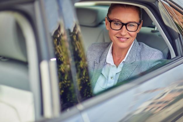 Feliz mujer de negocios de mediana edad con anteojos mirando por la ventana de un coche mientras está sentada en el asiento trasero, ella va a una reunión en taxi. concepto de transporte y vehículo, viaje de negocios.