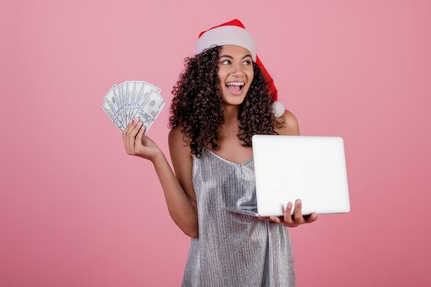 Feliz mujer negra con dólares y portátil con sombrero de santa vacaciones y vestido aislado en rosa