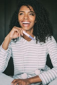 Feliz mujer negra con una prueba de embarazo en cama