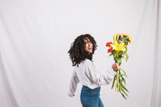 Feliz mujer negra con ramo de flores