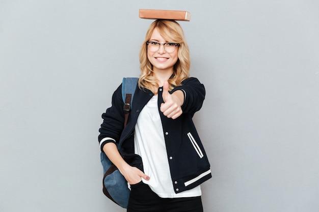Feliz mujer nerd en divertidas gafas con libro en la cabeza mostrando el pulgar hacia arriba
