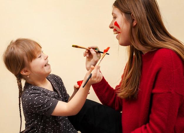 Feliz mujer y niña con síndrome de down pintando las caras del otro