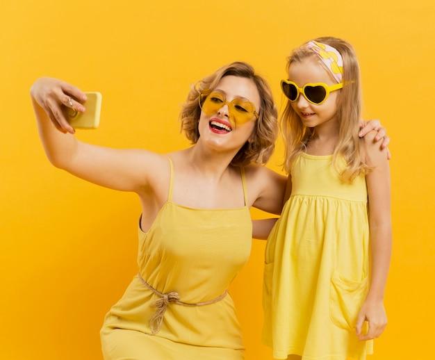 Feliz mujer y niña tomando una selfie mientras usa gafas de sol