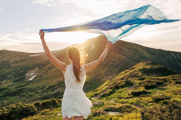 Feliz mujer con pañuelo en las manos siente la libertad y disfruta del paisaje de las montañas al atardecer