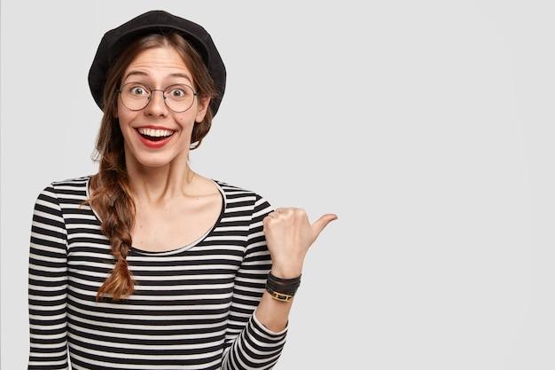 Feliz mujer parisina con sonrisa positiva, indica a un lado