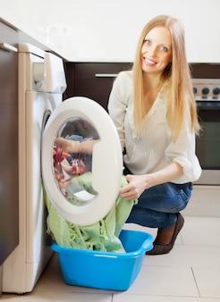 Feliz mujer de pelo largo cargando la ropa en la lavadora