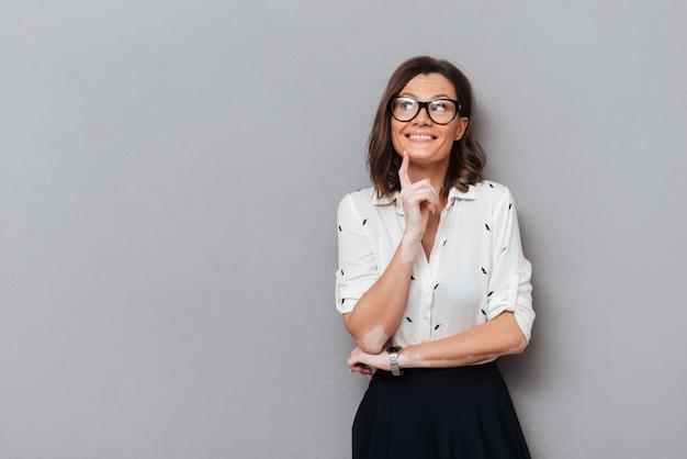 Feliz mujer pensativa en anteojos y ropa de negocios sosteniendo el dedo cerca de la barbilla y mirando a otro lado en gris