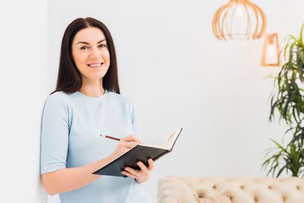 Feliz mujer de pie y escribiendo en el cuaderno
