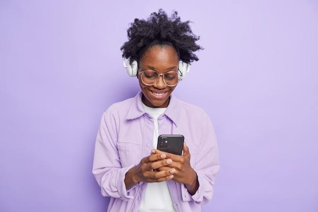 Feliz mujer de piel oscura sonríe alegremente lee el mensaje recibido escucha música a través de auriculares inalámbricos