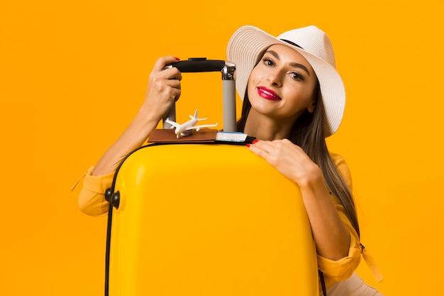 Feliz mujer posando con equipaje y estar listo para vacaciones