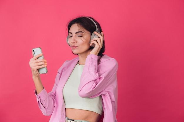 Feliz mujer positiva en auriculares en la pared roja rosa