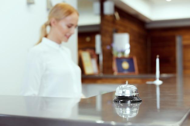Feliz mujer recepcionista de pie en el mostrador del hotel