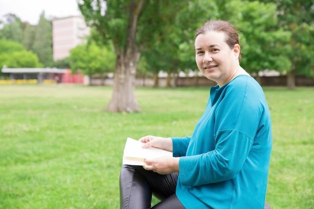 Feliz mujer relajada con libro disfrutando de fin de semana