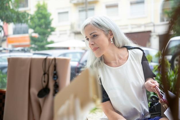 Feliz mujer relajada mirando los accesorios en el escaparate, sosteniendo bolsas de la compra, de pie en la tienda exterior. vista frontal a través del cristal. concepto de escaparate