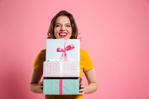 Feliz mujer riendo con labios rojos sosteniendo un montón de cajas de regalo,
