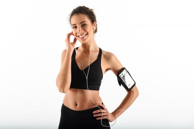 Feliz mujer rizada fitness morena sosteniendo el brazo en la cadera y escuchando música