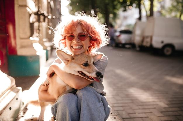 Feliz mujer rizada en jeans sonríe sinceramente y abraza a perro corgi
