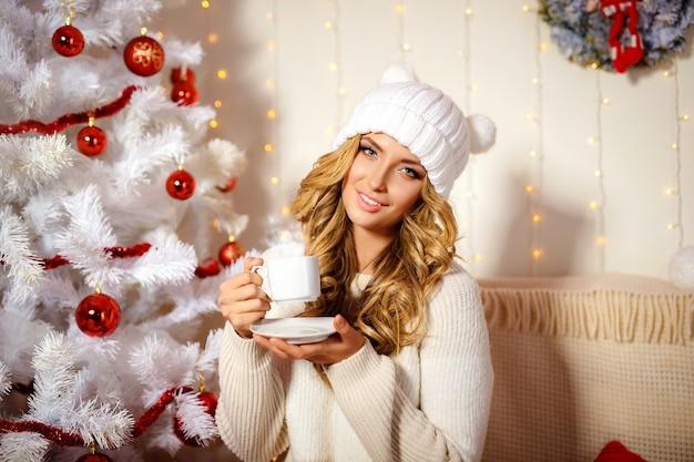 Feliz mujer rubia bebiendo café, habitación interior con decoración navideña
