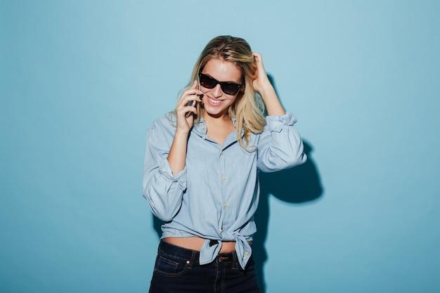 Feliz mujer rubia en camisa y gafas de sol hablando por teléfono inteligente