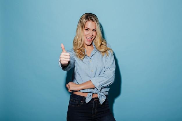 Feliz mujer rubia en camisa mostrando el pulgar hacia arriba
