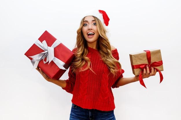 Feliz mujer rubia despreocupada celebrando la fiesta de año nuevo con regalos. vistiendo sombrero rojo de santa y suéter de punto. posando