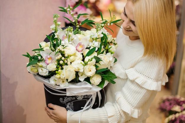 Feliz mujer rubia con una gran caja de flores de san valentín