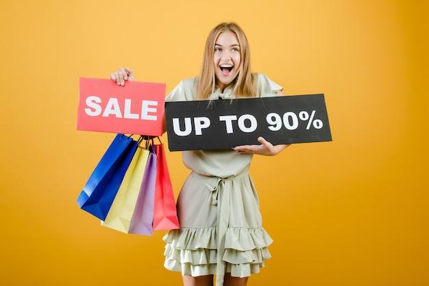 Feliz mujer rubia grita tiene venta hasta 90 signo con coloridas bolsas de compras aisladas sobre amarillo