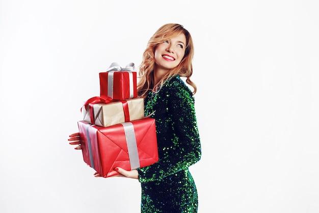 Feliz mujer rubia en increíble vestido de lentejuelas brillante con cajas de regalo de vacaciones sobre fondo blanco en estudio.