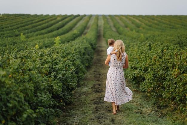 Feliz mujer rubia y lindo niño parado en el jardín de verano