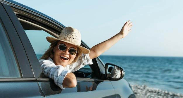 Feliz mujer rubia con sombrero mirando por la ventanilla del coche