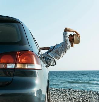 Feliz mujer rubia con sombrero de pie fuera de la ventana del coche