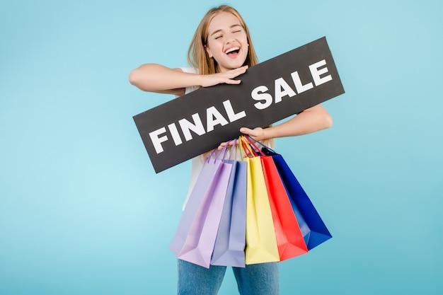 Feliz mujer rubia sonriente con cartel de venta final y coloridas bolsas de compras aisladas sobre azul