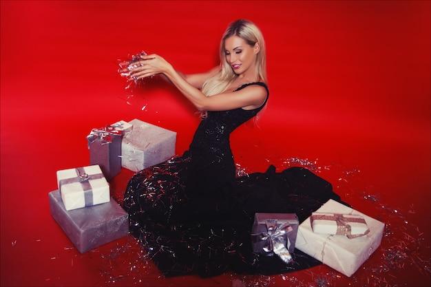Feliz mujer rubia sonriente en vestido largo negro con cajas de regalo y confeti cayendo sobre el fondo rojo aislado