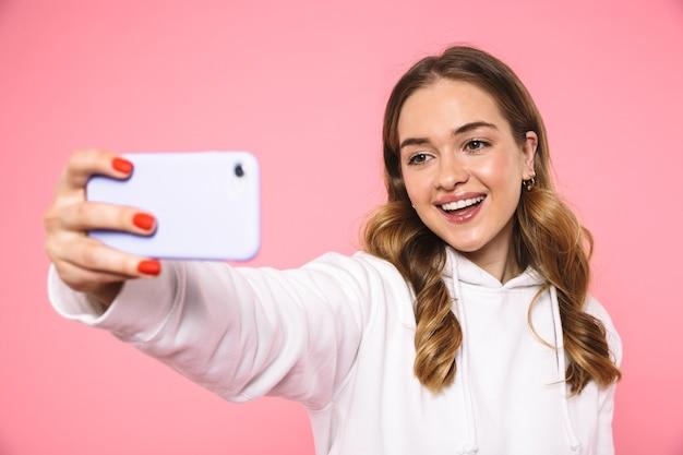 Feliz mujer rubia vestida con ropa casual haciendo selfie en smartphone sobre pared rosa