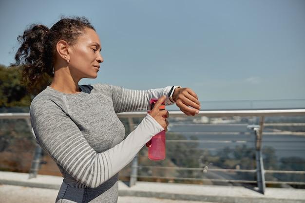 Feliz mujer sana y deportiva está bebiendo agua después de los entrenamientos de entrenamiento en un día soleado