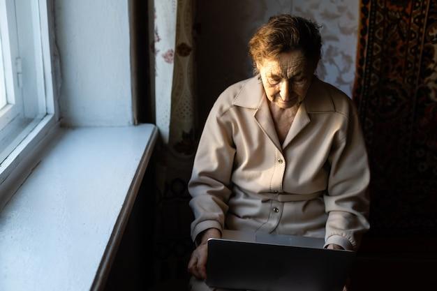 Feliz mujer senior sentada con su nieta mirando portátil haciendo videollamadas. señora madura hablando por webcam, haciendo chat en línea en casa durante el autoaislamiento. tiempo en familia durante corona