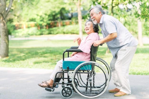 Feliz mujer senior en una silla de ruedas caminando con su esposo