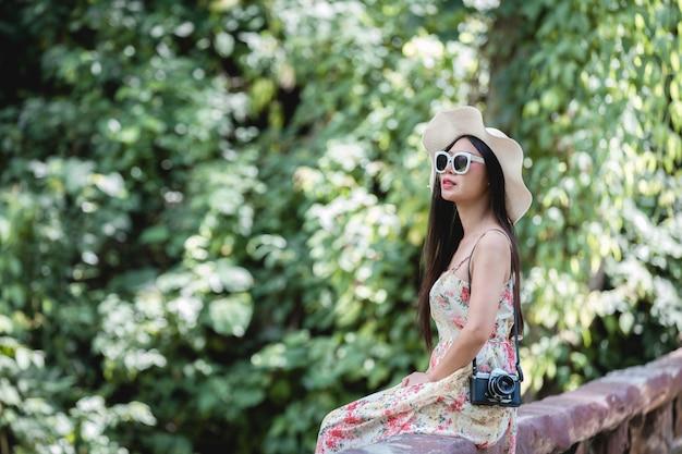 Feliz mujer sentada en la baranda en un parque