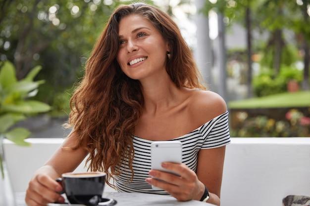 Feliz mujer sentada en una cafetería