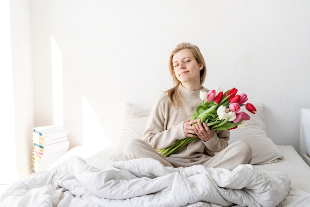 Feliz mujer sentada en la cama en pijama con los ojos cerrados, con placer disfrutando de flores y regalo romántico en el día de san valentín